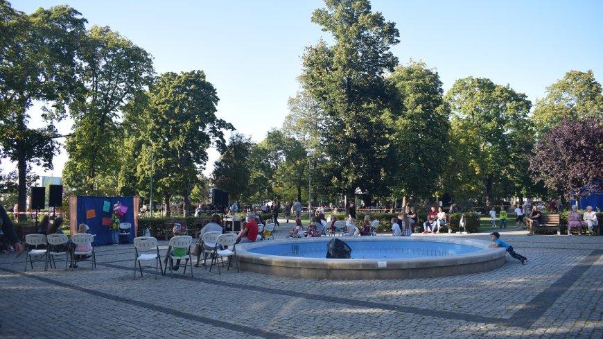 Na zdjęciu uczestnicy pikniku ekologicznego siedzący w Parku Miejskim wokół fontanny