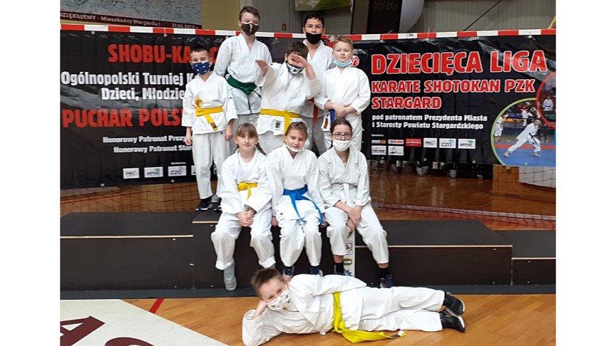 Wyniki z Ogólnopolskich Turniejów Karate - grudzień 2020 r. Na zdjęciu 9 osób w białych strojach, razem na podium w sali gimnastycznej.