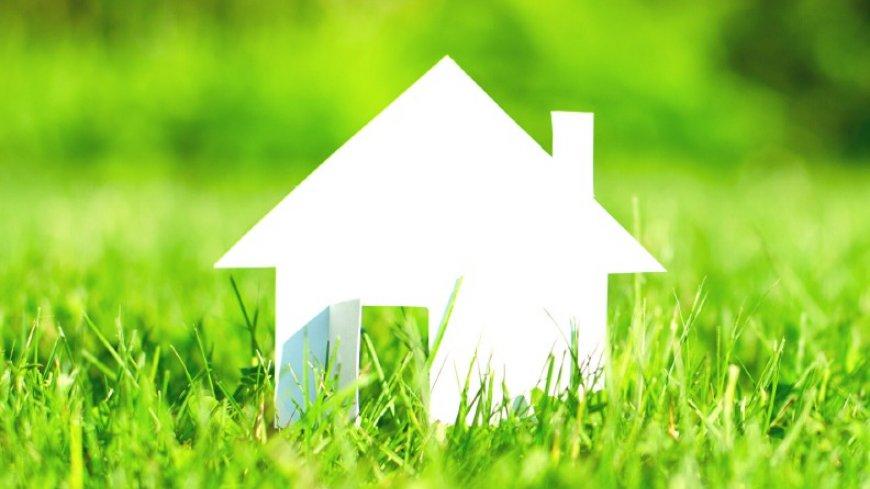 przykładowa grafika przedstawiająca biały papierowy domek na zielonej trawie