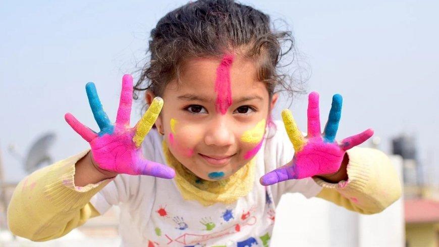 Dziewczynka z wystawionymi dłońmi pomalowanymi farbami.