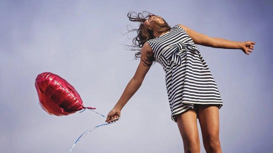 Dziewczynka w sukience w biało-czarne paski z czerwonym balonem w kształcie serca. Skacze, w tle widoczne niebo.