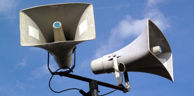na zdjęciu dwie tuby syren alarmowych na słupie - Fot. depositphotos